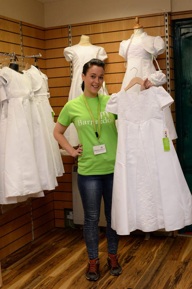 Joan Fitzgerald, shopworker, with some of the Communion Dresses for sale in Barnardos, Rathmines, Dublin