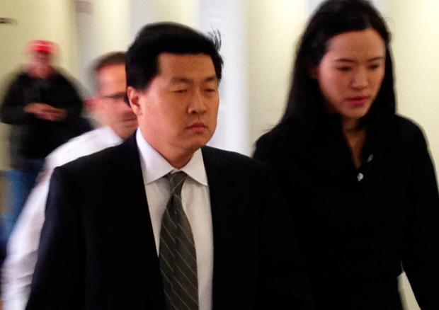 Former New York investment banker Jason Lee walks into court with his wife, Alicia