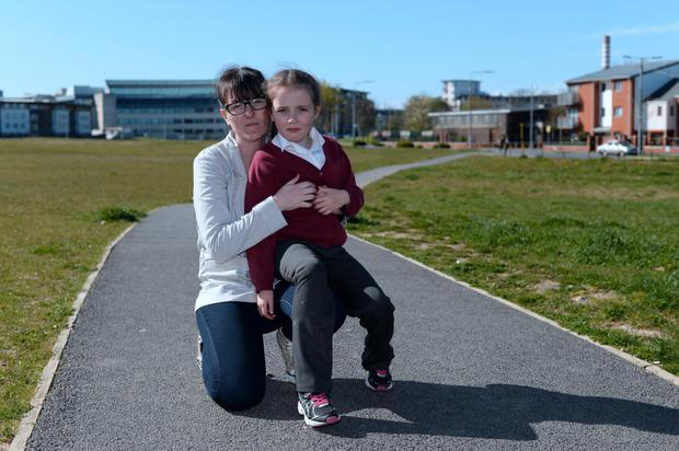 Helena McQuillan, 7, with her mother Mary, on pathway of small park off Shangan road where incident took place. Shangan road, Ballymun, Dublin