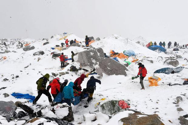 Sherpas, climbers, porters and rescue teams help carry a person injured by an avalanche that flattened part of Everest Base Camp. Rescuers in Nepal are searching frantically for survivors of a huge quake, that killed nearly 2,000, digging through rubble in the devastated capital Kathmandu and airlifting victims of an avalanche at Everest base camp.