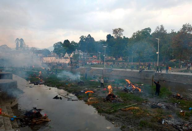 People burn the bodies of earthquake victims at a mass cremation in Kathmandu on April 26, 2015. Aid groups and governments worldwide intensified efforts April 26 to help earthquake-hit Nepal, but blocked roads, downed power lines and overcrowded hospitals posed formidable challenges in an already poor country