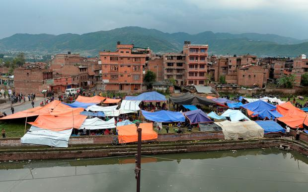 Nepalese people stay outside in tents in Bhaktapur on the outskirts of Kathmandu on April 26, 2015. International aid groups and governments intensified efforts to get rescuers and supplies into earthquake-hit Nepal on April 26, but severed communications and landslides in the Himalayan nation posed formidable challenges to the relief effort.