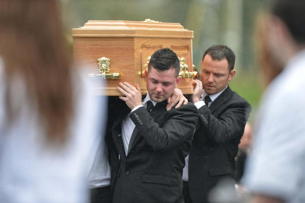 Brothers of Karen Buckley carry her remains past a guard of hounour of colleague nurses from UL, at Karen Buckley's funeral at St Michael's, Analeentha, Co Cork
