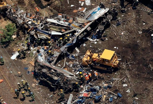 Investigators and first responders work near the wreckage of an Amtrak passenger train carrying more than 200 passengers from Washington, DC to New York that derailed late last night May 13, 2015 in north Philadelphia, Pennsylvania. At least five people were killed and more than 50 others were injured in the crash