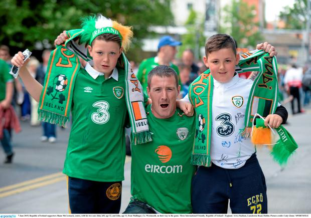 Republic of Ireland supporters Shane McCormack, centre, with his two sons John, left, age 12, and John, age 11, from Mullingar, Co. Westmeath, on their way to the game.