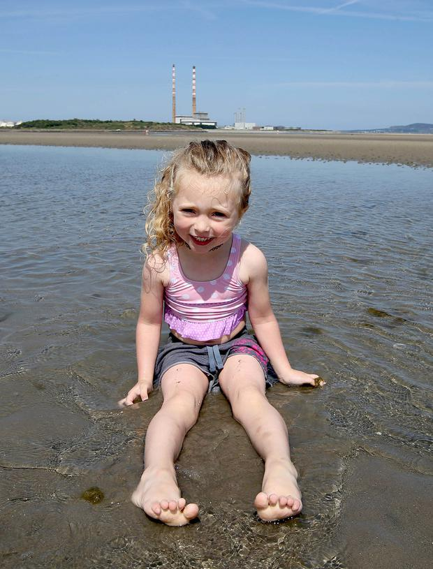 Cassie Dempsey, 4, from Dublin 8, enjoys the weather on Sandymount strand. Photo: Damien Eagers