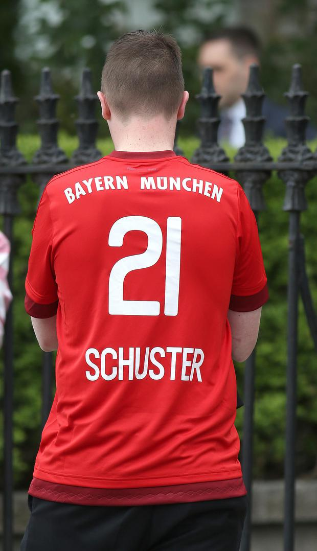 A mourner wearing a Bayern Munich jersey outside the Church of the Three Patrons, Rathgar for the funeral mass of Niccolai Schuster.