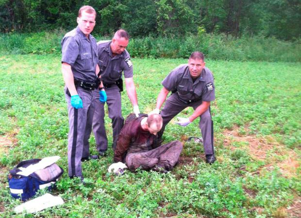 Police stand over David Sweat after he was shot and captured near the Canadian border Sunday, June 28, 2015, in Constable, N.Y. Sweat is the second of two convicted murderers who staged a brazen escape three weeks ago from a maximum-security prison in northern New York