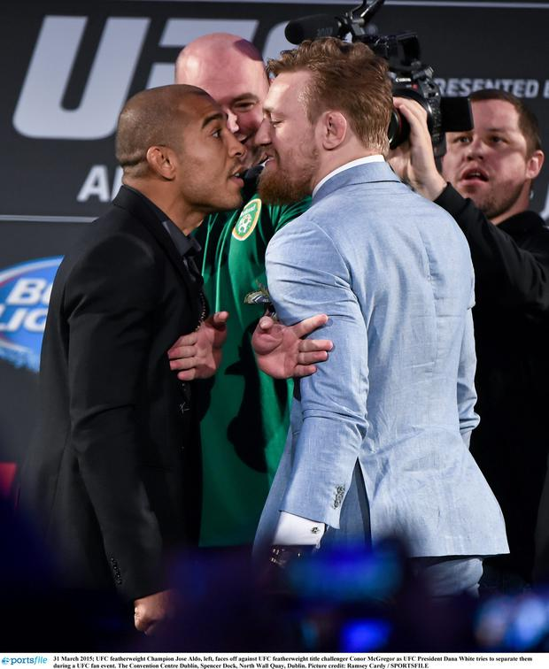 UFC featherweight Champion Jose Aldo, left, faces off against UFC featherweight title challenger Conor McGregor as UFC President Dana White tries to separate them during a UFC fan event.