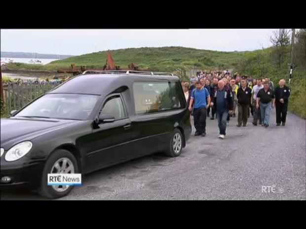 Rescuers and locals follow the hearse