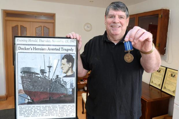 Cyril Deans with the medal and the Herald's coverage of his father's heroic act in 1958