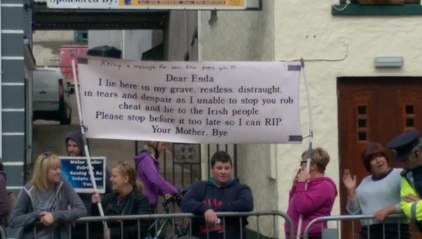 Protesters hold the banner up during the Taoiseach's visit of the Glenties