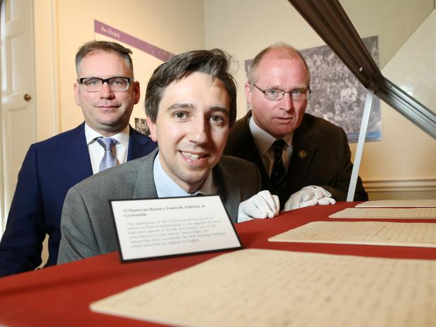 Minister Simon Harris – flanked by Brian Crowley of The Pearse Museum and Gabriel Doherty of the UCC Department of History – views the O'Donovan Rossa Funeral Oration Exhibition