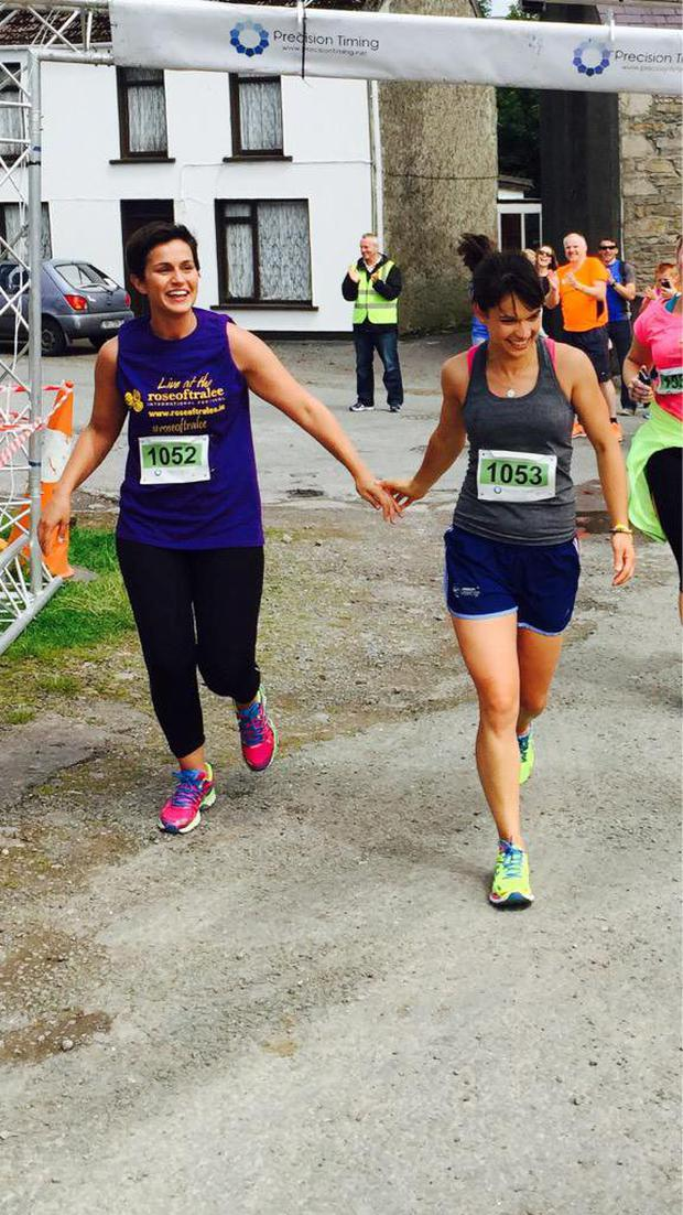 Rose of Tralee Maria Walsh crossing finish line in Annascaul 10k with personal trainer Jen Feighery ahead of Trek2Tralee
