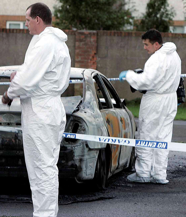 Gardai at a burned-out car after the murder of Mark Glennon
