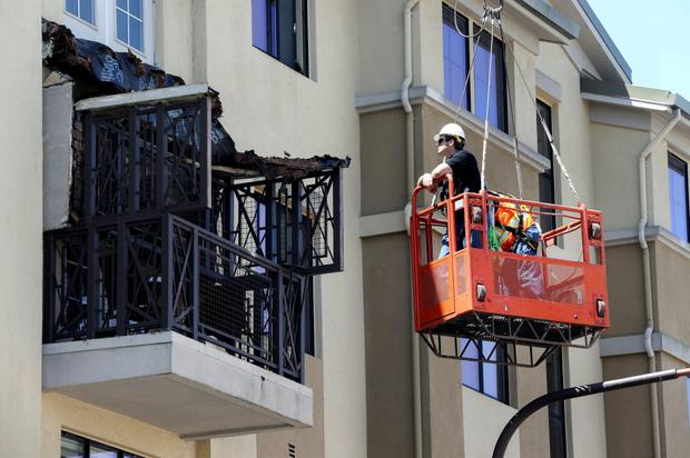 Workmen examine the damage at the scene of a 4th-story apartment building balcony collapse in Berkeley, California
