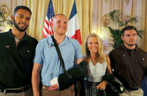 US ambassador to France, Jane Hartley, with student Anthony Sadler, US Airman First Class Spencer Stone and National Guardsman Alek Skarlatos (L to R) at the US Embassy in Paris