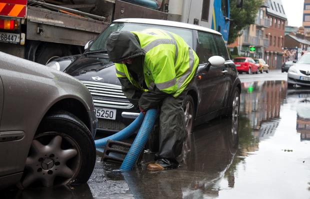Workers from the drainage services department try to unblock drains on Hogan Place, Dublin
