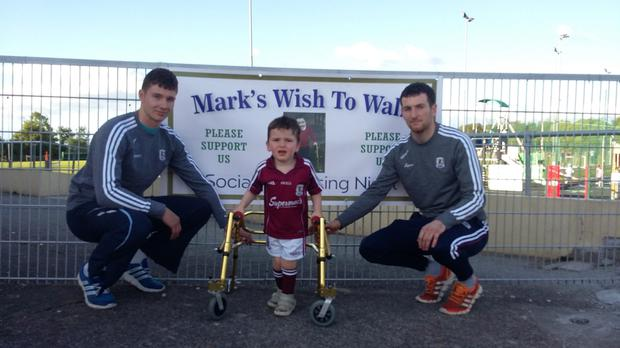 Galway hurling stars, Padraic and Cathal Mannion, take time from their All-Ireland final preparations to wish local youngster and fanatical Galway supporter, Mark Dolan (3), well as his family campaigns to raise €135,000 so he can undergo pioneering surgery in the US to allow him to walk