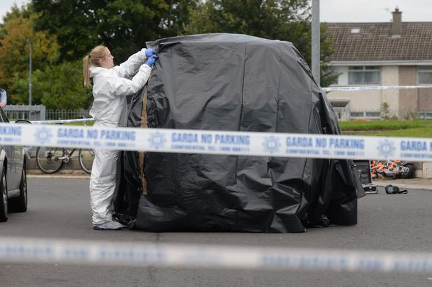A forensics expert covers a vehicle at the scene in Avonbeg Gardens in Tallaght yesterday