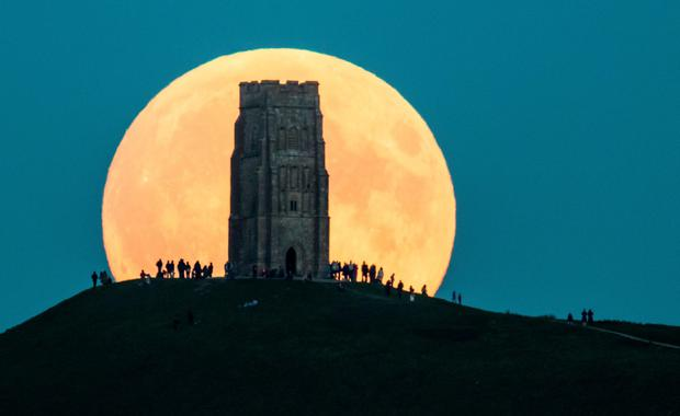 The supermoon rises behind Glastonbury Tor