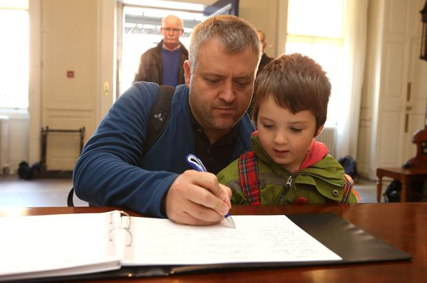 Fergal Treanor, and his son, Enda, 4, originally from Cabinteely but know living in Cologne sign the book of condolences to the victims of the carrickmines Fire tragedy. Picture credit; Damien Eagers 12/10/2015