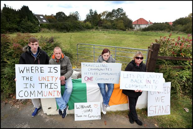 Protesters in favour of the halting site hold placards
