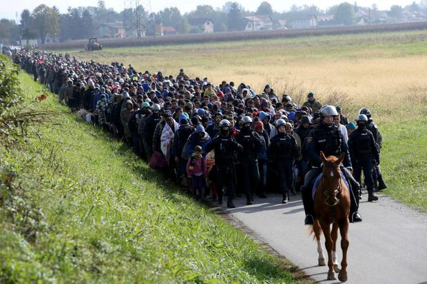 A mounted policeman leads a group of refugees as Slovenia sent in the army to deal with the crisis