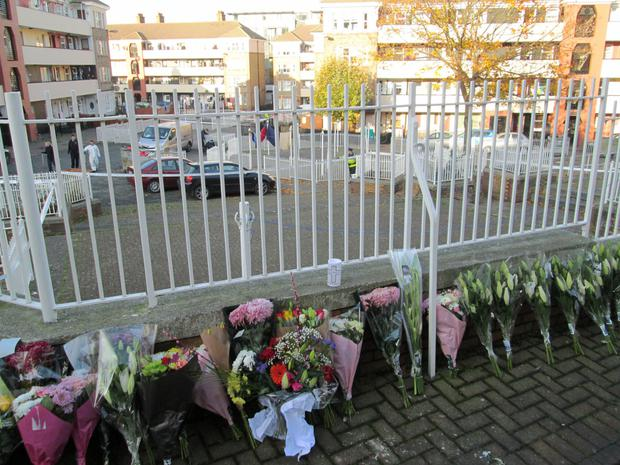 Floral tributes at the scene at Oliver Bond flat complex where Lorcan O'Reilly was stabbed; the teenage suspect has links to gangland figure 'Fat' Freddie Thompson