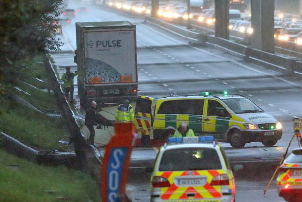A body is removed from the scene after a man was hit by a lorry on the M50