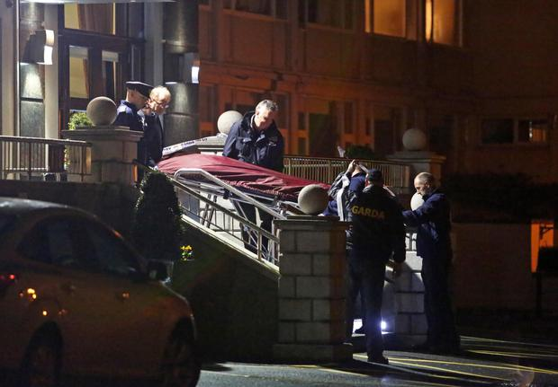 Gardai at the Regency Hotel in the aftermath of the shooting and (right) a body is removed from the scene (Collins)
