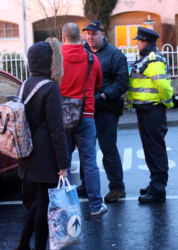 Gardai speak to shocked locals after the shooting (Collins)