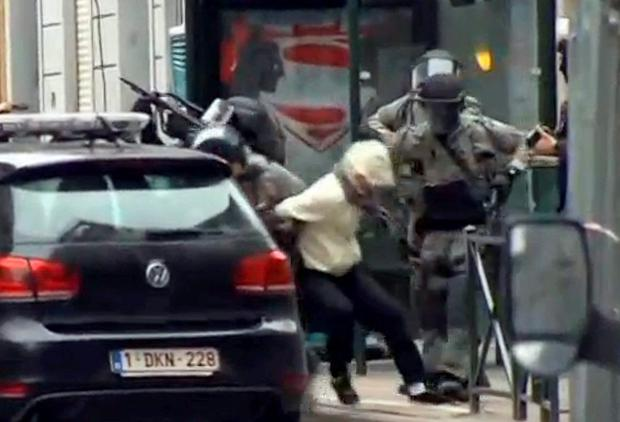 Belgian Police take a man during the raid. Photo: Reuters
