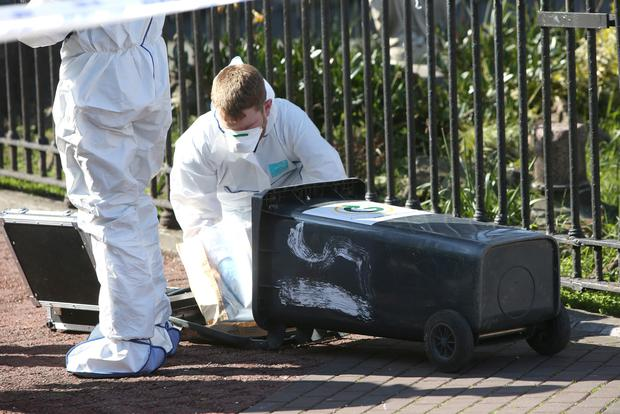 A garda technical officer examines a wheelie bin near the scene of Martin O'Rourke's murder in Sheriff Street (INM)