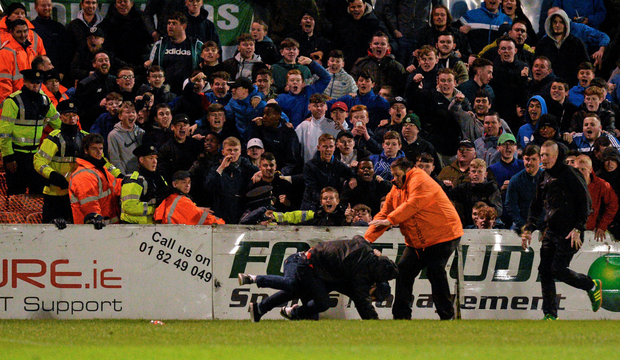 Spectators look on as stewards rush to control two fans who ran on to the pitch and began fighting. Photo: Sportsfile