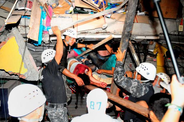 Rescue workers pull survivors from the rubble of a collapsed building. Photo: AFP/Getty
