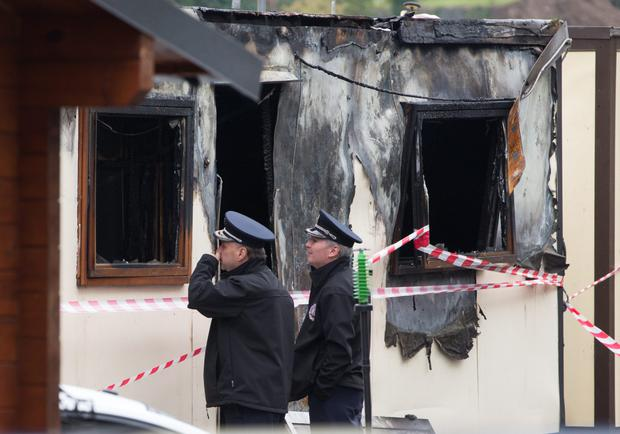 Fire officers inspect the scene of the blaze. Photo: Fergal Phillips