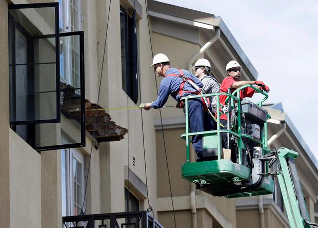 A crew work on the remaining wood of the apartment balcony that collapsed in Berkeley