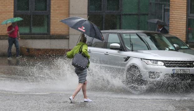 The torrential rain and resulting flash floods that hit Dublin caused havoc for pedestrians, motorists and trams Picture: Collins