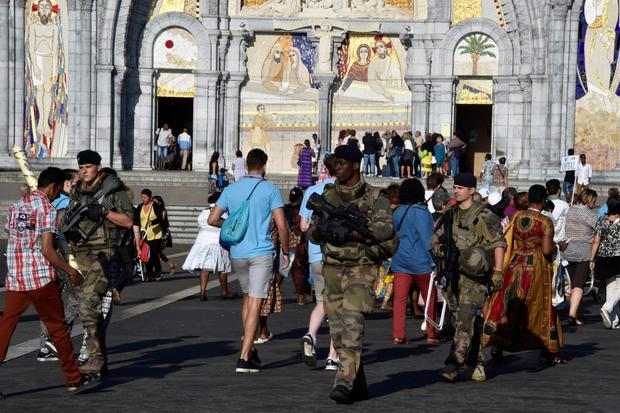 Soldiers and pilgrims mingle in the sanctuary of Notre Dame. Photo: AFP/Getty