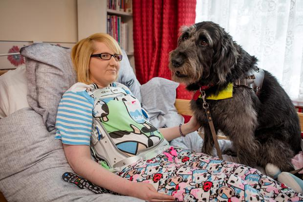 Elizabeth McNicholas, age 27, who is in need of an operation on her back in England, with her assistance dog Bart at her home in Lucan. Pictures:Arthur Carron
