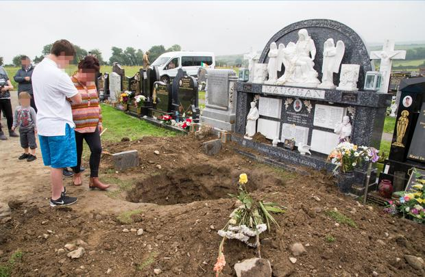 Family members beside the desecrated grave of Bobby Maughan at Bohernabreena Cemetry today Picture: Colin O'Riordan