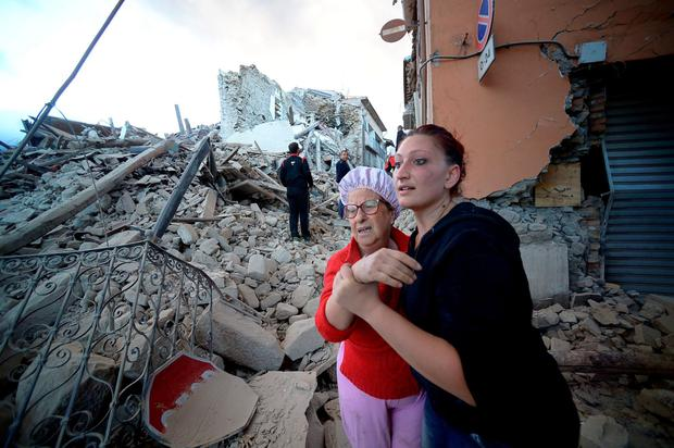 Shocked residents react among the rubble after the powerful quake devastated the town of Amatrice Picture: AFP