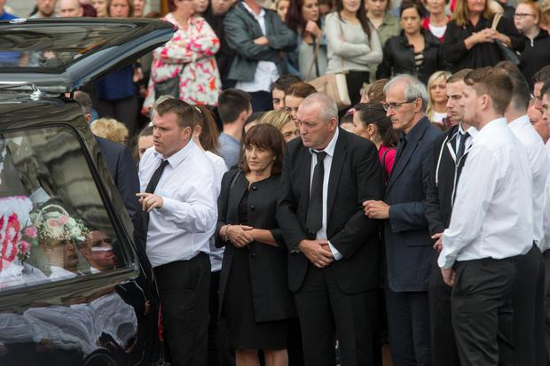 Her father, Patrick (grey hair) with friends and relatives follow the coffin from the church.