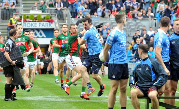 Dublin's Michael Darragh Macauley and Mayo's Keith Higgins tussle even before a ball is kicked as the teams enter Croke Park on Sunday.