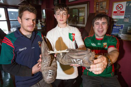 Michael Dawson with his grandfathers football boots and jersey from the 1951 All Ireland final that Mayo last won. Pictured with (from left) Barry Staunton and Michael McNeill in Leckanvy Co. Mayo.