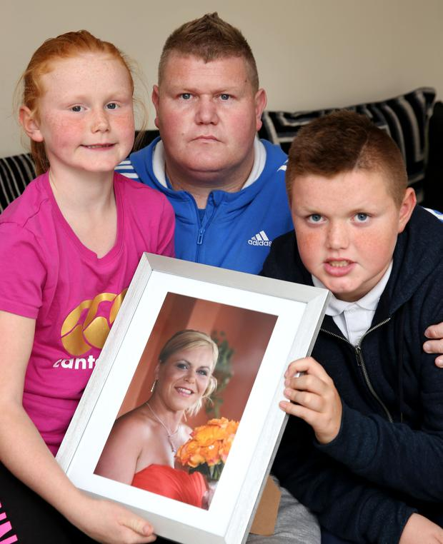 Codie, Brian and Adam Sherlock pictured with a photograph of their late mother and wife, Valerie Sherlock