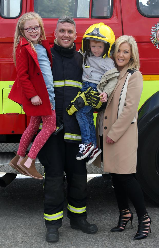 Firefighter John Walsh from Ratoath, Co. Meath pictured with his partner, Sarah Murphy and children, Mia (8) and Morgan (4) after he graduated as a full firefighter this afternoon at Dublin Fire Brigade Training Centre