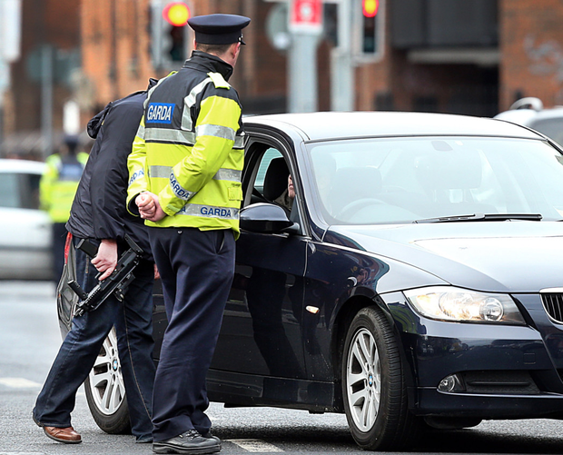An unarmed garda stands alongside a member of the ERU carrying a machine-gun at a checkpoint in the city centre Picture: Steve Humphreys