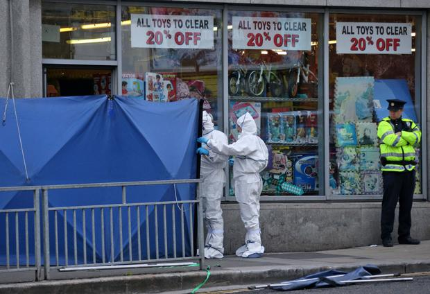 Garda forensic officers outside the shop in Bridgefoot Street where Daithi Douglas was shot dead